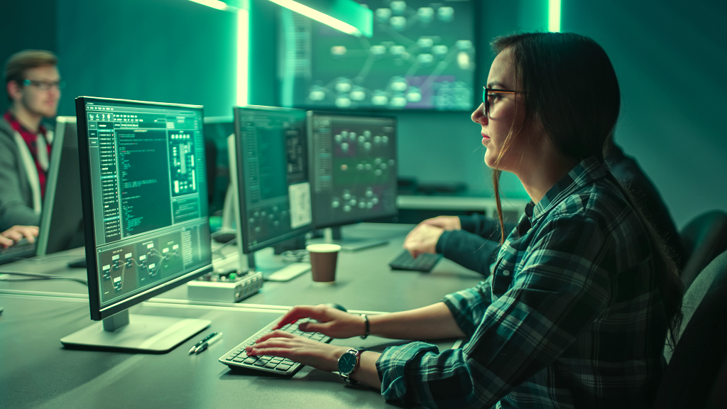 a woman sits in front of a computer in a dark, green-lit room