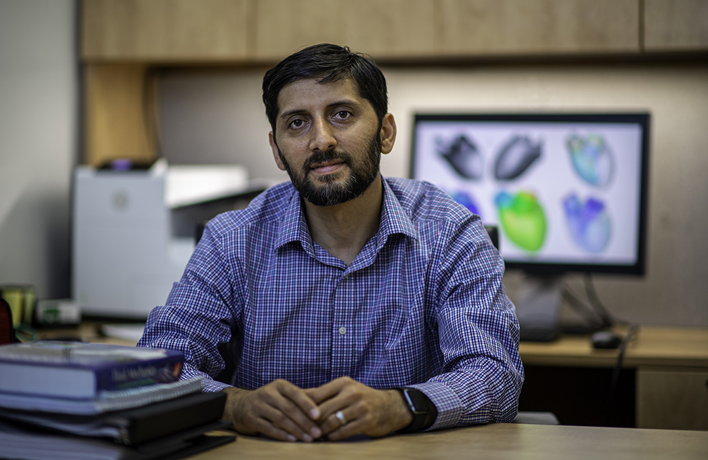 Hamid Sadat sits behind his desk, a stack of books to the left and a simulation on the computer in the background