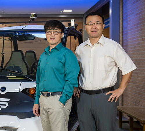 Qing Yang and Song Fu stand to the right of a connected and autonomous golf cart
