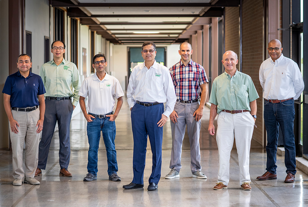 Raj Banerjee, Yijie Steven Jiang, Sundeep Mukherjee, Rajiv Mishra, Thomas Scharf, Rick Reidy and Nigel Shepherd stand in a hallway