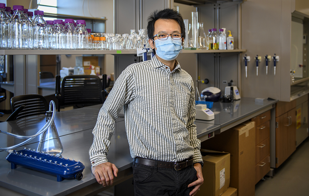 Clement Chan stands in the lab in front of a counter with vials