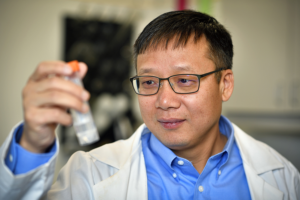 Jincheng Du eyes a sample in a test tube in his lab