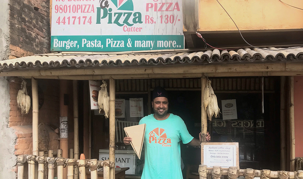 Prasanna Aryal stands in front of The Pizza Cutter holding a pizza shaped box