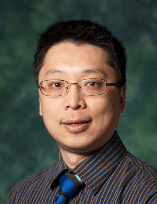 Zhenhua Huang poses in front of a UNT green backdrop.
