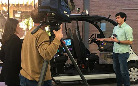 PhD student shows nearly autonomous vehicle to cameraman.