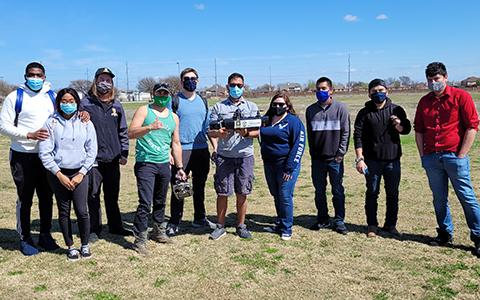 Ten students stand in a line outside with masks and pose while holding a drone and drone controller