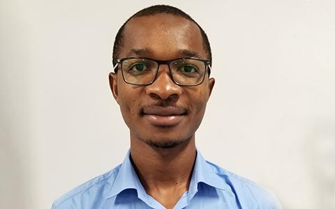 Aboubakar Mountapmbeme stands against a wall in a light blue shirt