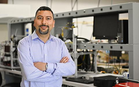 Huseyin Bostanci stands with arms crossed in his lab.