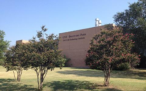 Photo features front of Discovery Park building with trees