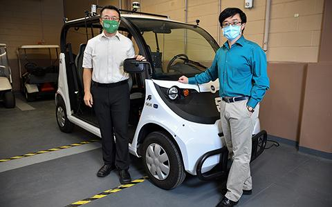 Song Fu and Qing Yang stand in front of an autonomous golf cart