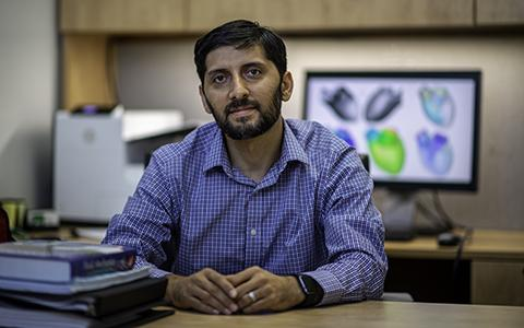 Hamid Sadat sits behind his desk, a stack of books to the left and a simulation on the computer in t