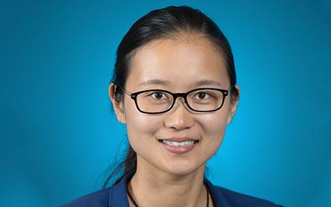 Junfei Xie headshot in front of blue background