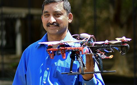 Kamesh Namuduri stands while holding a drone.
