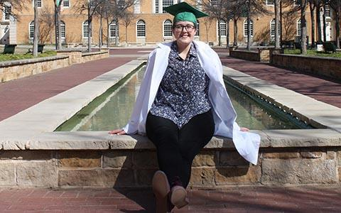 Kelly Jacques sits on the fountain ledge in front of the Hurley Administration Building.