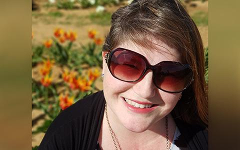 Melanie Dewey sits in a tulip field smiling