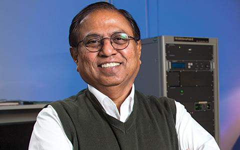 Narendra Dahotre stands in the lab smiling and with his arms crossed