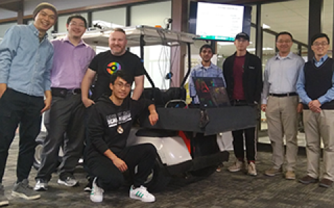 Yang and Fu posing with students in front of golf cart converted autonomous vehicle