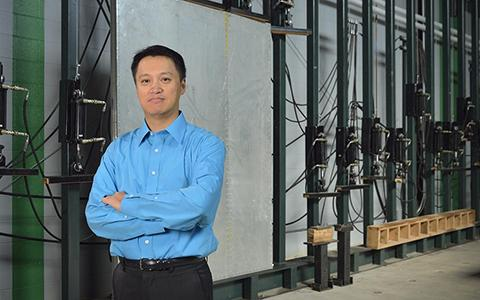 Cheng Yu stands in a lab with his arms crossed
