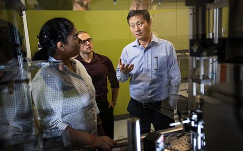 Tae-Youl Choi talks with students in a lab.