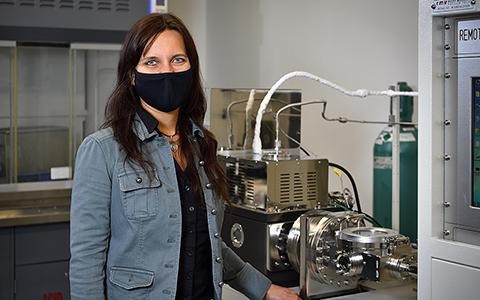 Diana Berman stands in front of machinery in a materials science lab