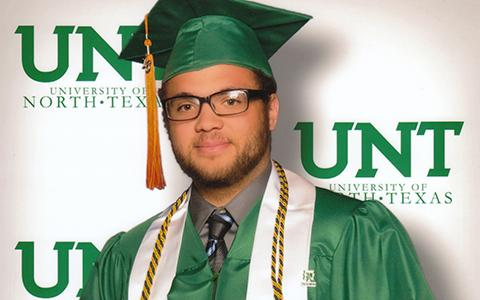 Jacob Montgomery Cole stands in a UNT graduation cap and gown, posing with his diploma frame in fron