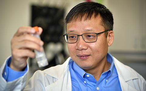 Jincheng Du holds up a test tube.